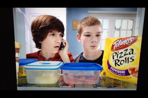 "I'm very sensitive to bad commercials. This Totino's Pizza Rolls ad is the absolute worst. Here's why:  1) It starts out with a kid calling his mom and saying, ""Mom. We're dying."" I don't care how much of your bullshit your mom has heard (which you can tell the mom has a TON of experience with by how she fucking flings it right back in their faces), you don't call your parent and tell them you're dying unless you're ACTUALLY DYING.  2) They say they can't find the Totino's Pizza Rolls when they're RIGHT. FUCKING. THERE. So, first they're trying to give their mom a heart attack and then they're too lazy to actually turn their heads to explore other parts of the fridge? These kids are dickholes.  3) As you can see in this photo, there is a container full of FRESHLY CUT WATERMELON RIGHT NEXT TO THE POCKET-SIZE DEATH KNOWN AS PIZZA ROLLS. Now, I know some kids don't like to eat fruit, but have you ever HAD watermelon?! It's fucking DELICIOUS. That shit is refreshing as FUCK. Hot summer day? Forget it - I'm all about watermelon. If there were any justice in this world, they would have looked down and been like, ""Oh shit, Mom, we have watermelon? Fuck pizza rolls."" AND THAT IS NOT EVEN THE WORST OF IT - the MOM probably straight knows there's watermelon there, and she still pushes them towards the pizza rolls?! That is a terrible dickhole mom. This is a family of dickholes. They represent the absence of dick within a dick.  4) THEY HANG UP ON THEIR MOM AND THEN PUT THE PHONE DOWN IN THE FRIDGE. They LEAVE the phone. In the fridge. After hanging up on the woman who gave them life. What the fuck?! What demographic is this commercial trying to reach? A: Dickholes.  I'm not going on some sort of anti-junk food rant. I'm going on an anti-stupid-people-writing-national-advertisements rant."