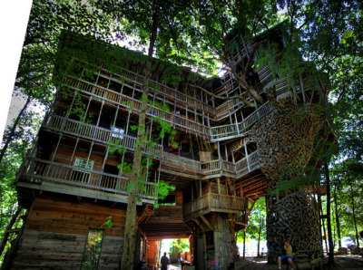 "hyperallergic:  ""The Minister's Treehouse in Crossville, Tennessee is a 100ft structure built by minister Horace Burgess from the early 1990s through 2004. The entire building wraps around a giant tree and was built completely without blueprints, sprawling to an estimated 10,000 square feet inside, including a four-story swing set."" [via Colossal (via Required Reading)  A key point, not mentioned above: Most of the building's lumber was reclaimed from ""garages, storage sheds and barns"" (as per this 2007 USAToday story). Pretty cool."