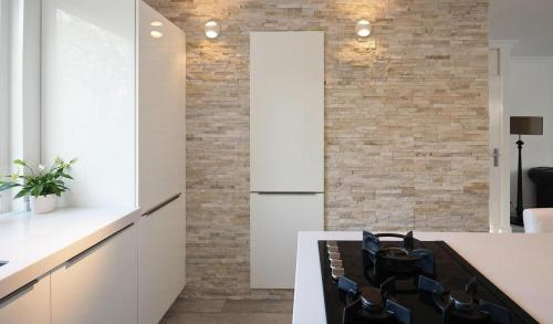 Nice integration of natural stone wall into a minimalist style kitchen!  sweethomestyle