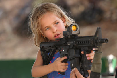 """Upon entering the range, his five-year-old daughter, Tamara, bursts into tears. A half hour later, she is holding a gun and shooting clay bullets like a pro."""