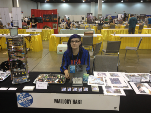 malloryhartart:  My booth and I from Denver comic con this weekend! It was a lot of fun, met awesome people and sold my work. Aaaaaaand I'll do it again next year.