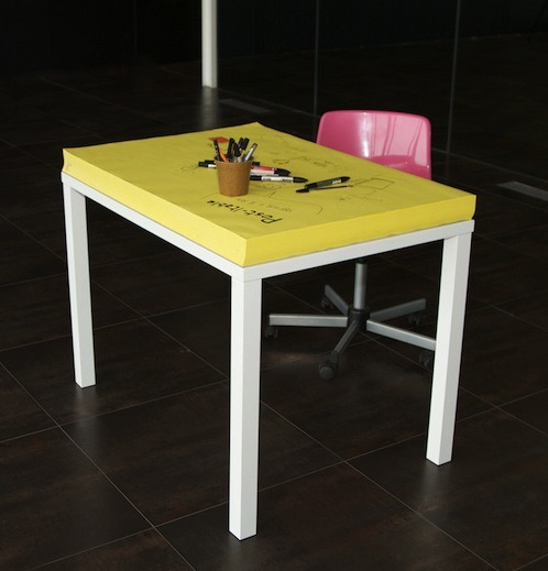 theatlantic:  Introducing the Post-It Desk, a Piece of Furniture You're Supposed to Draw On  When you're a kid, surfaces are made to be doodled on. Walls are crayon-canvases; wooden tables seem naked without some colorful finger paint prettying them up. It takes a while — from parents' perspective, a very long while — for us to learn to contain our decorational impulses. Creativity, we're gradually conditioned to accept, is best confined to paper. The lesson must be learned, but the learning is sort of sad nonetheless. And it's why I love this desk: a giant Post-it note that exists to be mucked up by random writings and drawings. The work of Lisbon-based designer Miguel Mestre, the desk is so retro that it's actually cutting-edge.  Read more. [Image: Designtaxi]