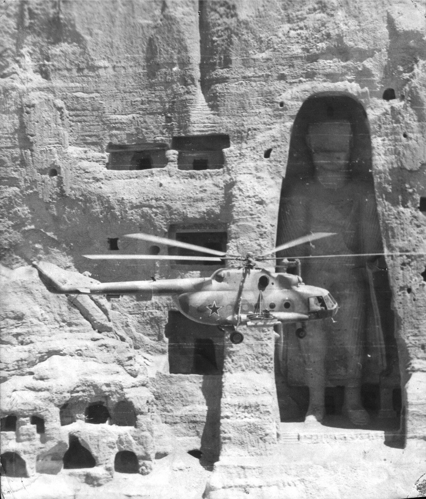 "dequalized:  A Soviet helicopter flying past one of the two Buddhas of Bamiyan in the Bamyan valley in the Hazarajat region of central Afghanistan, situated 230 km (140 mi) northwest of Kabul, 1980. The main bodies were hewn directly from the sandstone cliffs, but details were modeled in mud mixed with straw, coated with stucco. The statues were dynamited and destroyed in March 2001 by the Taliban, on orders from leader Mullah Mohammed Omar, after the Taliban government declared that they were ""idols"". International opinion strongly condemned the destruction of the Buddhas, which was viewed as an example of the intolerance of the Taliban. On 8 September 2008 archeologists searching for a legendary 300-metre statue at the site of the already dynamited Buddhas, announced the discovery of an unknown 19-metre (62-foot) reclining Buddha, a pose representing Buddha's passage into nirvana."