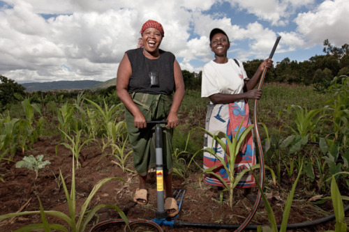 Penniah and Ann demonstrate to gathering farmers how to use a Kickstart pump. Learn more at theadventureproject.org.