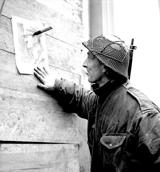 kampfgruppe:  Soldier of the 2nd Canadian Infantry Division looks at a portrait of Hitler hanging on the wall of a house with a knife. 28th Feb 1945, Calcar, Germany.