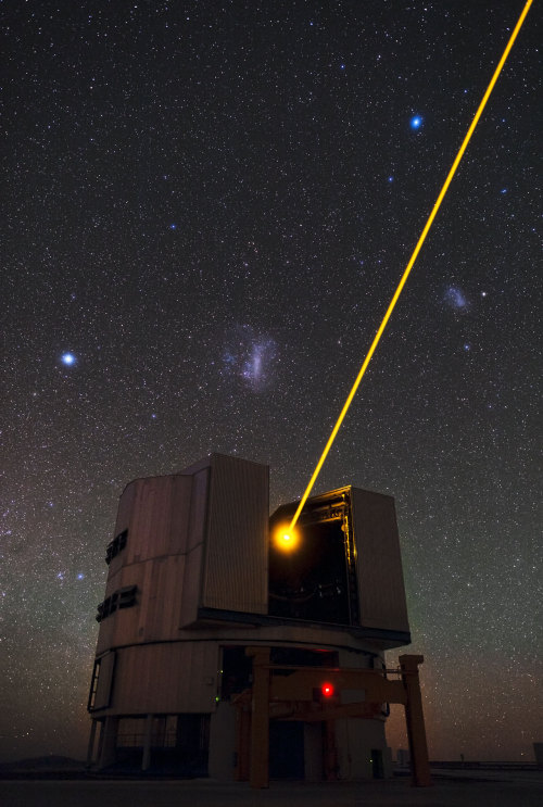 the-star-stuff:  Yepun's Laser and the Magellanic Clouds This spectacular image shows Yepun, the fourth 8.2-metre Unit Telescope of ESO's Very Large Telescope (VLT) facility, launching a powerful yellow laser beam into the sky. The beam creates a glowing spot — an artificial star — in the Earth's atmosphere by exciting a layer of sodium atoms at an altitude of 90 km. This Laser Guide Star (LGS) is part of the VLT's adaptive optics system. The light coming back from the artificial star is used as a reference to control the deformable mirrors and remove the effects of atmospheric distortions, producing astronomical images almost as sharp as if the telescope were in space. Credit: ESO/B. Tafreshi/TWAN