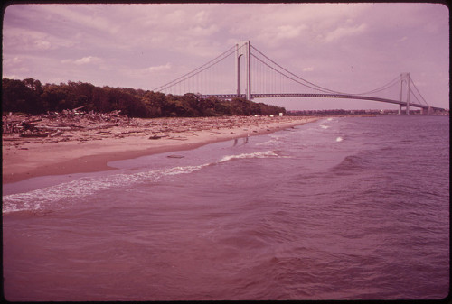 Original caption: The Verrazano-Narrows Bridge Crosses New York Bay and Connects Staten Island and Brooklyn 06/1973. Photo by Arthur Tress.  The debris-covered beach speaks sad volumes.