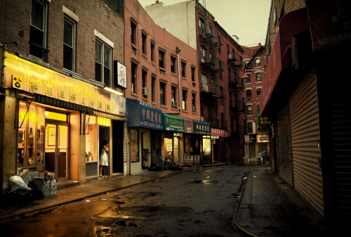 "Doyers Street on a rainy summer afternoon. Chinatown, New York City.  When the sky seduces the city with its tears of happiness, the streets swoon illuminated by the glow of nearby lights.  Broken-hearted alleys fill up: lovers with empty recesses in their hearts soak in the warm afterglow of what the sky has wrought.  —-  View this photo larger and on black on my Google Plus page  —-  Buy ""The Seduction of the Sky - Doyers Street - Chinatown - New York City"" Prints here, email me, or ask for help."