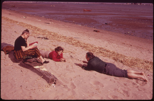 Original caption: Plum Beach at Sheepshead Bay 05/1973. Photo by Arthur Tress.  Hey, you three! Get up and start cleaning up that beach!