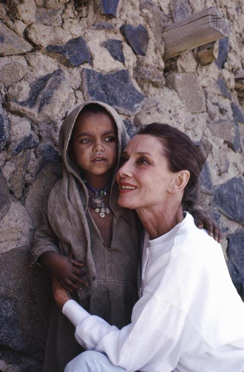 UNICEF Goodwill Ambassador Audrey Hepburn hugs a small girl who is standing in the shade of a large stone wall in the town of Mehal Meda in the northern part of the province of Shoa, Ethiopia. In 1988, internationally known film actor and UNICEF Goodwill Ambassador Audrey Hepburn travelled to Ethiopia on her first official UNICEF mission, to raise awareness of the impact of the continuing drought on the country's children and women. During her trip, Ms. Hepburn visited UNICEF-assisted health clinics and supplementary feeding programmes, 'food-for-work' projects, an income-generating project and an orphanage for children who have been abandoned or orphaned in this region during the drought. © UNICEF/NYHQ1988-0194/John Isaac http://www.unicef.org