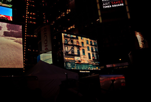 "My photography in Times Square for Artists Wanted. 43rd and Broadway. Midtown, New York City.   Yesterday was quite a day! It started off when I was notified that this article/interview with me about my photography was published online which then went (mildly) viral during the course of the day: Shooting New York City, heart, art and soul .   To top it all off, I ended up taking a little trip in the evening uptown to Times Square to view my photography on a nice size screen in the middle of 43rd Street and Broadway as part of the Artists Wanted contest!   I wish I had known which screen my photo was going to show up on because I would have positioned myself on that side of the (very crowded) staging area but this photo will have to do. I was so stoked that I burst into a huge and slightly ridiculous joker-smile that must have been so over-the-top that a woman standing next to me nudged me and said ""Oh! That must have been your work up there, eh?"" with a grin. I guess I couldn't quite hide my crazy excitement :).  You can view the photo of mine that was chosen from the portfolio I submitted here. I was really pleased that they chose this particular photo out of the nine photos in my contest portfolio since it holds a lot of sentiment.   —-  View this photo larger and on black on my Google Plus page  —-  Buy ""In Another Place and Time - Chinatown - New York City"" Prints here, email me, or ask for help."