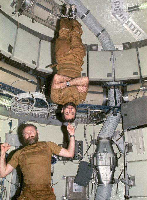 Monkeying around in Skylab  Astronaut Gerald P. Carr, Commander for the Skylab 4 mission, jokingly demonstrates weight training in zero-gravity as he balances astronaut William R. Pogue, pilot, upside down on his finger.