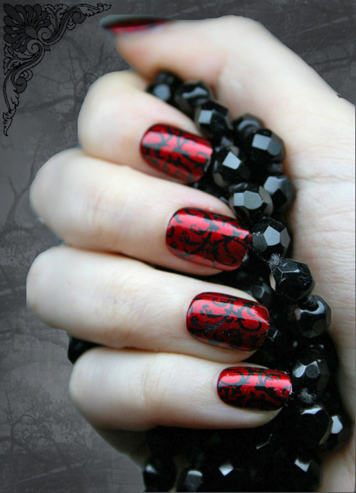 Goth-inspired nails with a pop of bright red.