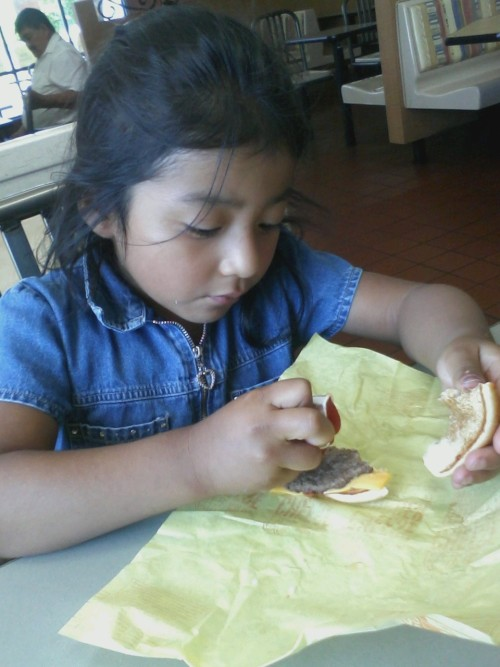 It's Cutee How She Eats Her Hamburgers :D