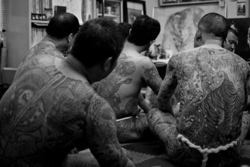casual gathering of naked tattooed men.