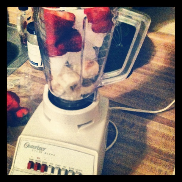 This is happening - bananas, strawberries, ice, honey, a splash of cranberry juice, and a spoonful of vanilla yogurt.  (Taken with Instagram)