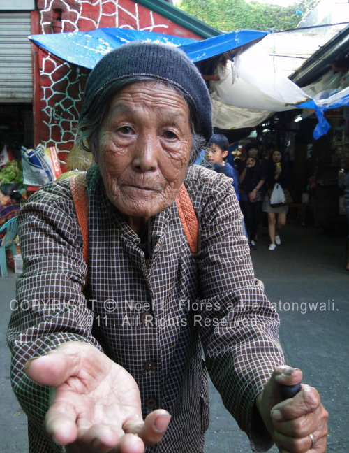 This is an image of a Buenguet Beggar roaming around the Baguio Public Market. It's just sad how tourism transformed our once proud highland natives into beggars.           - It's all over the world, but it's just sad to see your own people,    tribes, clans, etc, who once prospered in so much, broken down, due the modern technology and such.