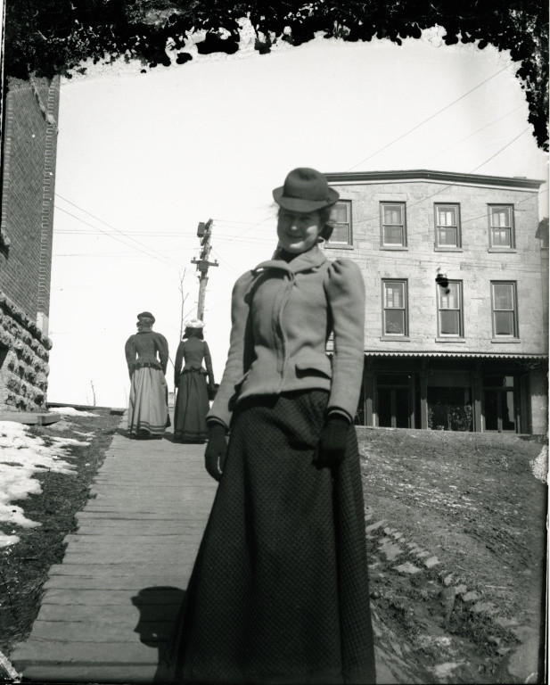 "Henry Alley at High Street, Mineral Point, Wisconsin, ca. 1900. Three women contend with Mineral Point's impressively hilly landscape as they ascend a board sidewalk to High Street. The street's name—High Street, not Main Street—reflects the influence of the Cornish settlers who came to the community in the 1830s and 40s. ""The High Street"" is the common term for the main business street in British towns. via: Glass Plate Negative Collection, Mineral Point Historical Society"