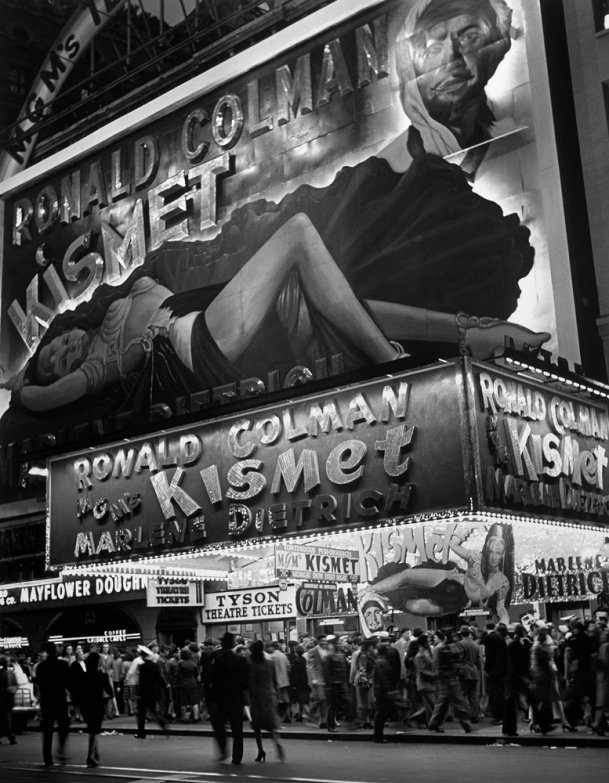 New Yorkers crowd Broadway below a large billboard depicting actress Marlene Dietrich in October 1944. By Andreas Feininger