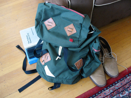"My Kelty Backpack Although I typically use a soft, leather briefcase as my everyday work bag, it's hard to get by as a graduate student without a backpack. Sometimes I just have a bunch of things I need to lug around, such as books or packages, and the larger compartmental space inside a backpack simply makes more sense. So a few months ago, I bought this green Kelty ""Mockingbird"" backpack after seeing a picture of Pete Anderson with it outside of a menswear tradeshow. Most of Kelty's backpacks are very practical looking – neither horrifically ugly nor very attractive. In the last few years, however, they've been releasing designs quite similar to those they had in the 1960s and '70s. As many know, this has been a response to the Americana/ outdoor gear fashion trend in Japan. It used to be that you could only get these bags if you were in Japan, or at least went through a proxy shopping service, but nowadays Americans can have their Americana as well. Kelty's neovintage bags stay mostly true to their original designs. They just have a few modern updates. For example, whereas the original Keltys used to have just one large compartment, this one has an interior pocket for your laptop (which fits my 13"" MacBook quite well) as well as zippered pockets both inside the main compartment and in the fold-over flap that covers it. There are also detachable cylindrical pocket bags you can attach to the sides. I keep one on to hold a thermos I sometimes use when I go to campus.     My only gripe is that it's somewhat of a hassle to open and close if you're in a hurry. There are two metal ladder locks to hold down the fold-over flap, as well as a drawstring closure to keep the main compartment closed. If you're running a little late, these can be kind of a bother to deal with, but I suppose you could also leave them open without too much danger. The fold-over cover should be enough to deter thieves. Photos of the bag online make it look kind of silly, but only because they stuff it so much that it looks like some kind of mini-jet pack with thrusters on the sides. In practical use, I think it's quite handsome. With its vintage inspired design, it's obviously a fashionable backpack, but not one that looks overly fancy. It also allows someone like me, a 33-year old grad student, to wear a backpack without feeling like he's on his way to social studies class.   (As an aside, Jesse was selling this amazing Japanese mountaineering backpack sometime last year. It sounded like it was too big for my purposes, but boy – did it look great)."