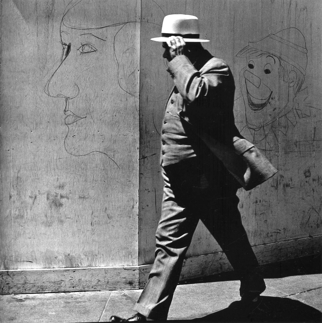 John Gutmann: Man Walking by Clown and Lady Graffiti, San Francisco, 1939