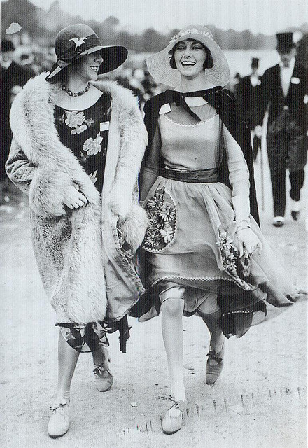 "Ascot, 1928 on Flickr.  Click image for 772 x 1123 size. ""At Ascot in 1928 the woman on the right has chosen to wear a softer, more elegant dress with sheer and floral detailing similar to the picture dresses fashionable at the beginning og the Twenties. Her wide straw hat is more suited to this look than a sleek cloche might be."" Scanned from the book ""Decades of Fashion""."