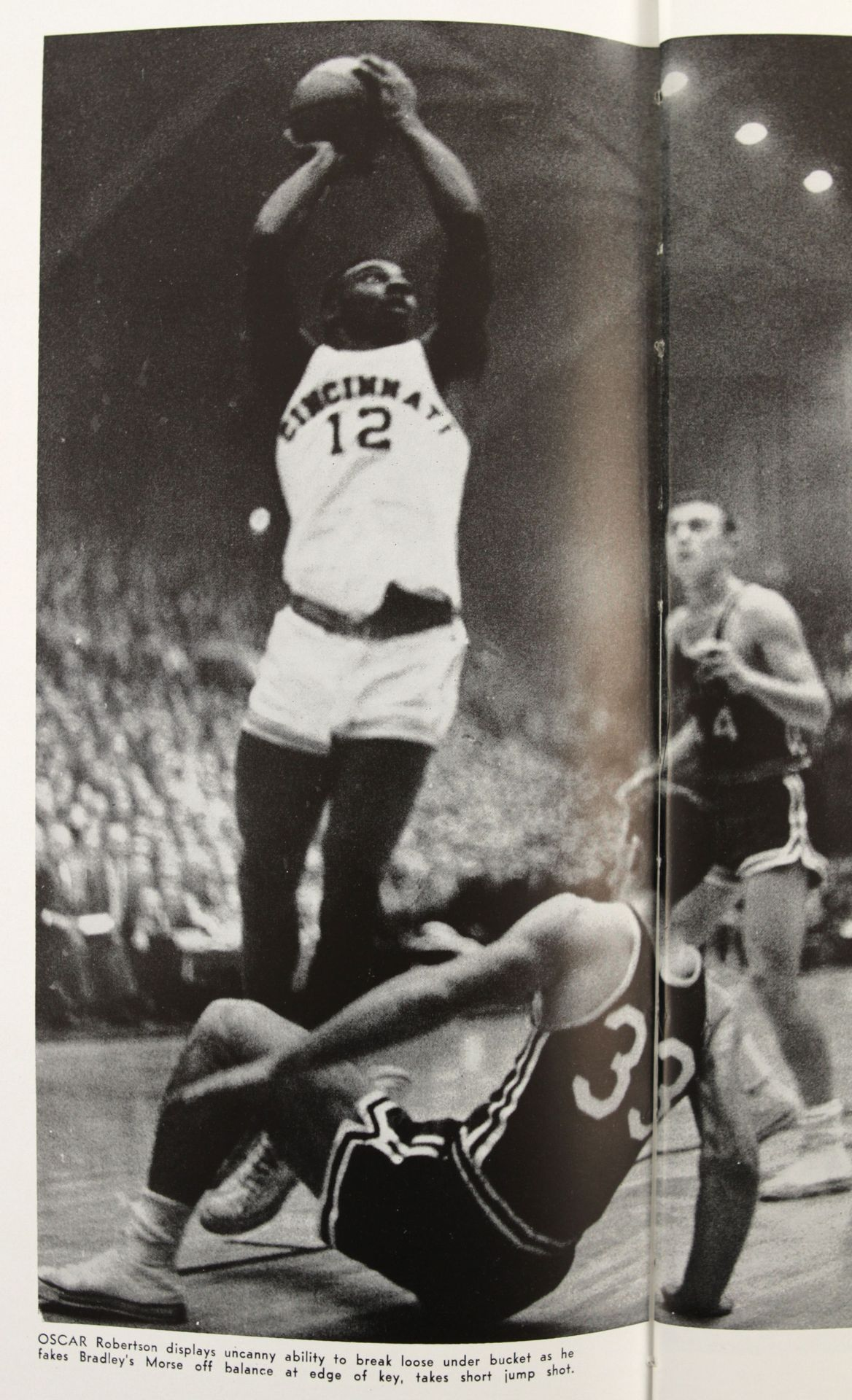 """OSCAR Robertson displays uncanny ability to break loose under bucket as he fakes Bradley's Morse off balance at edge of key, takes short jump shot."""