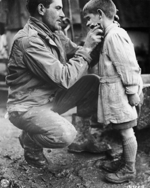 American soldier Walton Trohon cleans the face of a young French orphan, 1944. LIFE