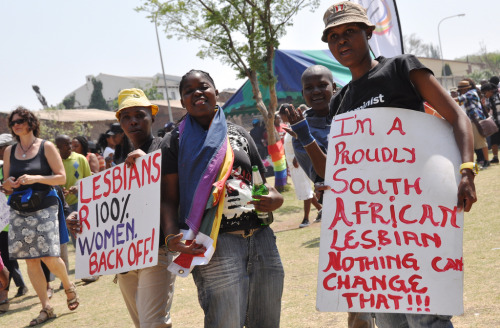 "[Image: Photo of several dark-skinned women at a pride event, two of whom are holding signs. One sign reads, ""Lesbians R 100% women. Back off!"" and another reads, ""I'm a proudly South African Lesbian nothing can change that!!!""] 100% Lesbian (by Lauren Barkume) ""At the 7th annual Soweto Pride March, held in Meadowlands, Soweto, South Africa. The march is held in the location of the brutal murders of 2 lesbians 4 years ago. The goal of Soweto pride is to ensure that lesbians in the township no longer fall victim to homophobic attacks."" from 2010"
