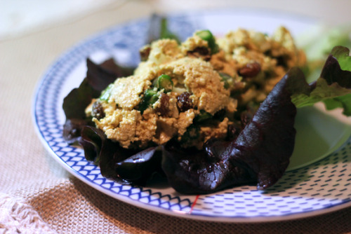 Eggless Egg Salad – With Curry, Asparagus, and Raisins Ingredients 1 Package Extra Firm Tofu 5 Asparagus Stalks ½ Small Onion ¼ Cup Raisins ½ Cup Vegan Mayo 3 Tsp Curry Powder ¼ Tsp Cinnamon 2 Tsp Lime Juice 2 Tsp Agave Salt & Pepper to Taste  Directions The first thing you want to do is drain your tofu really well. To do so, cut the tofu in half to make two thin slabs. Wrap both halves tightly in a paper towel, pressing any water out as you do so. Then pile a heavy cutting board on top, weigh it down with any other heavy objects you may have, and let it sit for 20 minutes. Chop asparagus and onion, and toss them in a bowl with the raisins. Unwrap your tofu. Crumble it with your fingers and add it into the bowl. Mix in all other seasonings and ingredients using a fork. Place the eggless egg salad in the refrigerator overnight and serve the next day. *For a beautifully shot, image-by-image set of instructions, click the image above