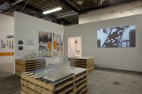 """A 'Vertical' Future for the Urban Factory NATE BERG JUNE 21, 2012 If the question is ""belching smokestack?"" the answer is almost undoubtedly ""not in my back yard."" The factory is maybe the least enticing of all neighbors, and yet it has been so important to the development of nations and cities. So while the industrial revolution brought countless factories and their plentiful jobs into cities, those same cities eventually got tired of their negative, sooty externalities. Zoning quartered them off into their own little corner of the city, and a long list of other conditions – from racial tensions to union squabbling to the migration of workers to looser regulations – eventually pushed many of these factories beyond the borders of cities and out into the exurbs or overseas. A new exhibit at the Museum of Contemporary Art in Detroit tells the story of the urban factories left behind, and how this city may once again become home to a vibrant collection of manufacturing centers. ""Vertical Urban Factory,"" which runs through July 29, sees this urban future of manufacturing largely in its urban past. Through a detailed and architecturally-focused history, the exhibit tracks the urban roots of the factory, highlighting its role in developing the economies and cultures of places.  ""The factory contributes to the city both in terms of sources of labor, places for people to work, but also as a kind of vital space where things are being made and things are happening,"" says curator Nina Rappaport.  This show was originally shown in New York City in early 2011. For Rappaport, taking it to Detroit was an obvious step. In September, it will move on to the Toronto Design Exchange. As it did in Detroit, the Toronto version will add a new section featuring factories from that city, such as old breweries and distilleries and the sugar refinery that's still operating there. The now-decaying 1922 Packard automotive plant in Detroit, the 1926 Fiat factory in Turin, Italy, and the 2006 Volkswagen factory in Dresden, Germany, all make appearances. By showing examples of both old and currently operating urban factories, Rappaport tries to remind us that manufacturing still has a place in modern cities. ""One of the things that's so frustrating is that many urban mayors think that nothing's being made in cities anymore,"" says Rappaport. ""There's thousands of factories in New York. And hundreds in Chicago and Detroit. They're still there."" Via: The Atlantic Cities Photo: Corine Vermeulen, courtesy of MOCAD"