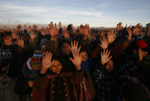 lukut:  People raise their hands to receive the first beam of the rising sun during the winter solstice ceremony in Tiahunaco, 70 km (44 miles) from La Paz, June 21, 2012. The solstice coincides with the Aymara Indian New Year.