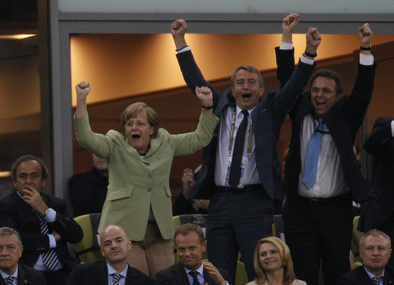 UEFA President Platini looks on while German Chancellor Merkel and DFB president Niersbach celebrate during the Euro 2012 quarter-final soccer match between Germany and Greece at the PGE Arena in Gdansk. [REUTERS/Peter Andrews] READ MORE: Germany crushes Greece to reach semis