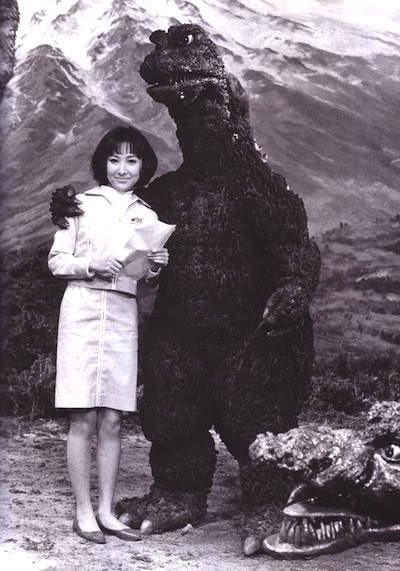 "mangacritic:  criterioncorner:   Yukiko Kobayashi and Godzilla on the set of DESTROY ALL MONSTERS. words cannot describe how much i love this picture. especially how disgruntled Godzilla looks, like he's just going through the motions and waiting for his next coffee break. tragically, the photographer forget to turn off the flash, and there were no survivors.   There are three things about this photo I love: Godzilla looks almost… furry. Yukiko Kobayashi is wearing a pair of stylish yet sensible shoes, ideal for outrunning monsters who are flattening Tokyo. The monster head in the foreground: did Godzilla just kill it, or is it sneaking up on him and Yukiko?  —- If Godzilla was a real celebrity, this would happen all the time.  ""Look, can we just hurry this up?"""