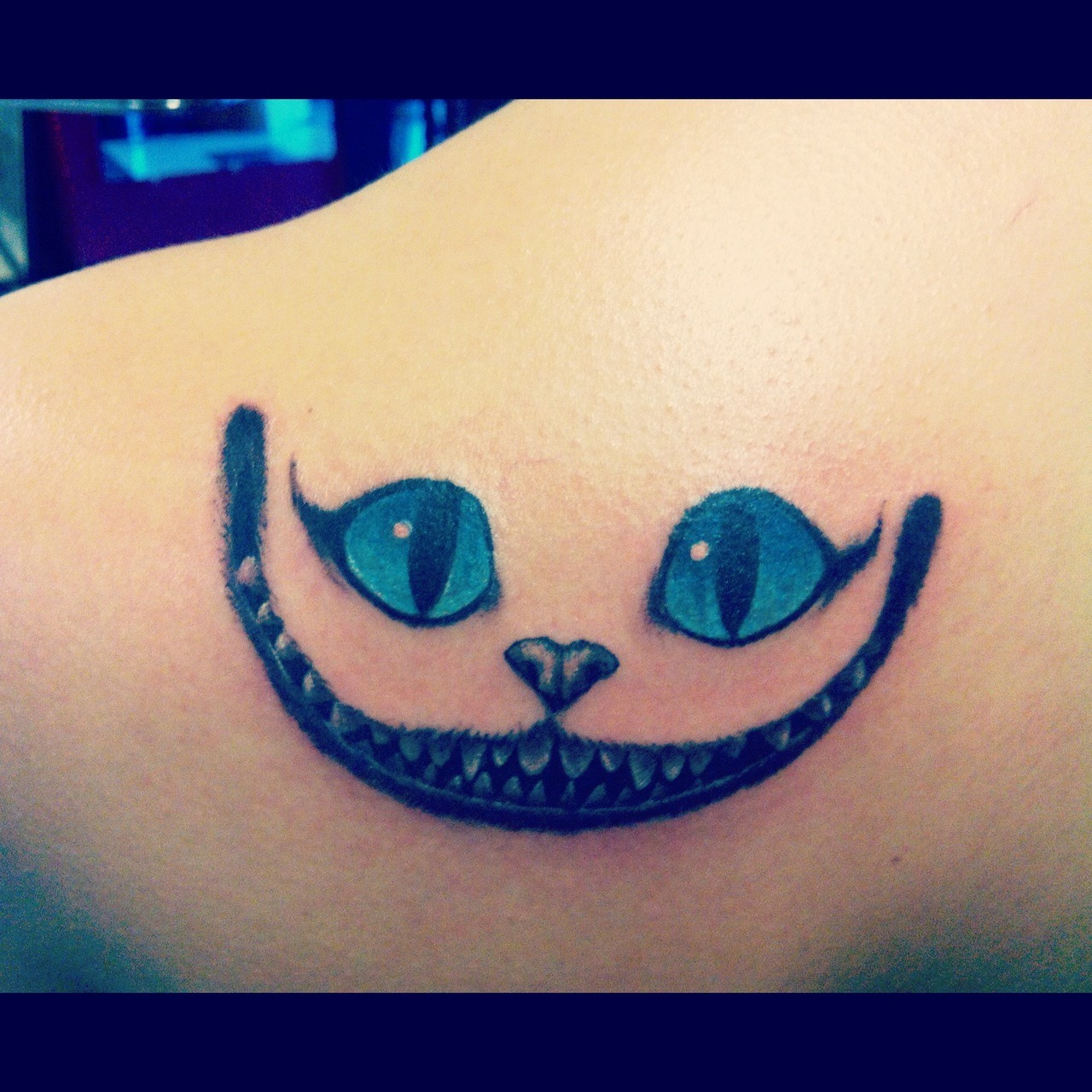 "fuckyeahtattoos:  This was my second tattoo and it's the cheshire cat from Alice in Wonderland. I got it pretty shortly after I got my first one, which is ""We're all mad here"" on my collarbone. They are just so perfect and fitting together. I'm so happy with the way they both came out. Done by James Moral at Anchor's Away  Nice"