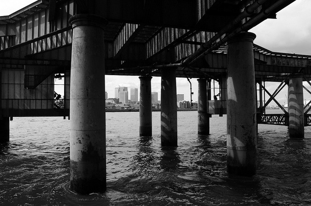 andthemoonrose:  Under the jetty on Flickr. Canary Wharf through the legs of the large coal jetty (now unused) at Greenwich Power Station