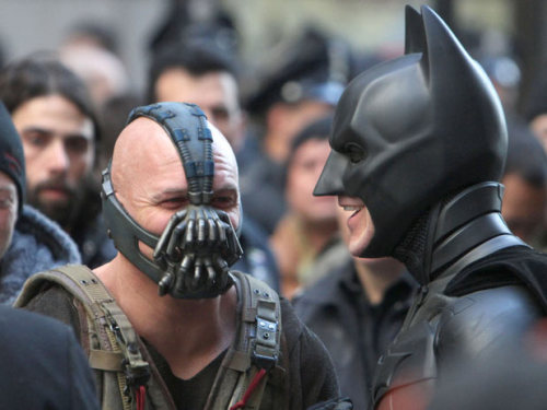 "charlidos:  From the production notes for The Dark Knight Rises - all the Tom Hardy bits:  Tom Hardy—who dons body armor and a bulky breathing mask as the menacing villain Bane—recalls precisely that moment.  It happened in the midst of a massive crowd scene on Wall Street in Manhattan, during a fight sequence between their two characters.  ""It was the first time I ever heard Christian say he was tired,"" Hardy remembers.  ""I was watching him for however many months getting beaten up and wet and cold, and he never said anything.  Inside, I was dying, but I was thinking, 'This can't bother me because he's not bothered.'  But on Wall Street, he just turned and said, 'You know what?  I'm exhausted.'  I said, 'Me too.'""""We stopped the fight and started hugging each other,"" Bale adds.    […] Tom Hardy agrees, noting, ""The thing about Chris is that he creates such a safe place to work, but it's also challenging because this is a guy who flips trucks for real.  So, you never know what you're going to be asked to do.  There are all kinds of pressures involved in a movie like this.  It's like test-flying a brand new aircraft for the military.  There's pressure that you're going to crash it.  But at the end of the day, if I opted out of the pressure then I wouldn't be doing my job."" Hardy plays Bane, the film's destructive villain who presents a real threat to Gotham City and to Batman. ""Bane is a serious piece of kit,"" Hardy describes. ""He's not there to joke. He's come to do business and there's no frivolity or messing around. It's very blunt and militant, very aggressive from the start."" Nolan agrees, calling Bane ""extremely efficient. He's driven by a very specific set of actions and plans. Nothing is wasted. He's much more of a physical adversary. In the first two films, we'd never presented Batman with a physical challenge, somebody who would literally stand toe-to-toe with him and battle in a physical sense. That's an important part of who Batman is.  He's trained in fighting. He has honed his body. He's an incredibly physical hero. So, we really wanted him for the first time in our movies to meet his match in somebody who's truly a monstrous figure."" After working with the director on Inception, Hardy leapt at the chance to do another film with Nolan and signed onto The Dark Knight Rises without even reading the script. ""Chris actually called me on the phone and said, 'Tom, there's a character you might be quite good for but I'm not sure if it's something you'd be interested in because it's going to demand you to wear a mask, and I appreciate that as an actor you probably wouldn't want to wear a mask for six months,'"" the actor recalls. ""He couldn't tell me anything about the character, just that he had a mask and he was a bad, very bad guy. And I said, 'Let me get this straight. You want me to come away and work with you around the world and I have the use of an entire stunt team and as many weapons as I want for six months and all I have to do is wear a mask?' He was like, 'Yeah, pretty much.' So, I said, 'I'm in.  Absolutely,'"" Hardy laughs.   The actor sees the mask as an indelible part of Bane's identity. ""If you look at mask work over history, they all have their own character,"" he says. ""Each mask is built specifically to draw out a specific character in Italian theater and whatnot. So, actually, a lot of the work is done by being camouflaged. You're not self-conscious."" That camouflage came in handy for some of Hardy's more intense stunts. ""I was on a walkway, holding onto the side of a building and very delicately walking out onto a platform about sixty feet high,"" he remembers with a wry smile. ""I wasn't very manly, or masculine without the mask.""  ""Bane is a phenomenally strong-minded character,"" Bale adds. ""So, you've got to be bold, and you've got a bold actor right here. Tom goes the distance. I mean, he goes way beyond what most other actors would do. He's created a phenomenal villain."""