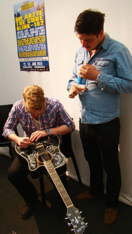Marcus Mumford and Ted Dwane of Mumford & Sons sign a guitar for the Hagstrom Guitar Contest at Hurricane Festival in Scheesel, Germany on 23rd June 2012. Photo courtesy of CampFM.