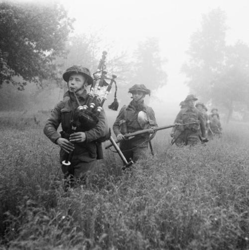 Led by their piper, men of 7th Seaforth Highlanders, 15th (Scottish) Division advance during Operation 'Epsom' in Normandy, 26 June 1944