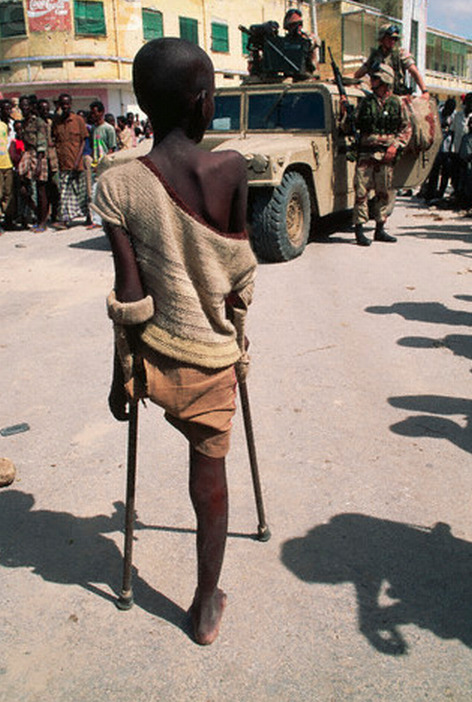 "simply-war:  Mogadishu, Somalia: A one-legged boy stands with his crutches and watches American soldiers patrol along the Green Line, which was a heavily contested area during the civil war. In the 1980s a civil war erupted in Somalia when warlord factions joined together to overthrow then president Siad Barre, who finally lost power in 1991. Since then power struggles between warlords have ravaged the country with famine and violence. US and international troops entered Somalia to provide aid and presence as part of ""Operation Restore Hope"" in December of 1992. © Peter Turnley"