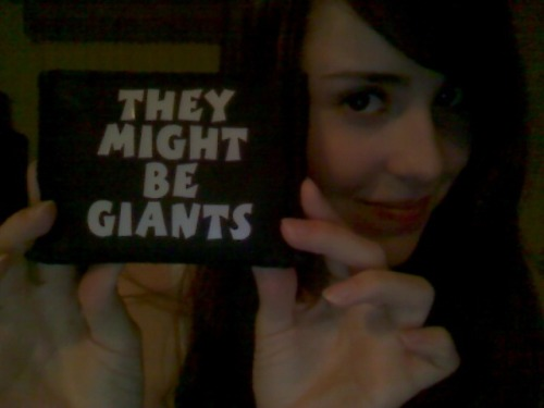 hellononagon:  My trusty TMBG wallet that I got 7 years ago at a show. Unfortunately, it's falling apart and I don't think they make them any more. :(  Those were SO COOL but yeh, nooooooooooot at all sturdy. I went through two of the red ones, and have one of them on my desk with my other very special merch cos it's signed by The Johns. I wish they did more random merchandise like that—t-shirts are great and all but other stuff is so fun.