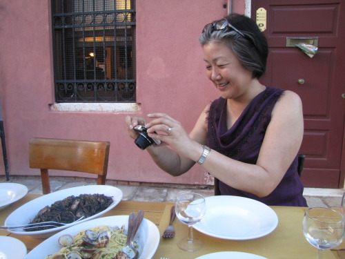 My mom in Venice, delighted by the spaghetti stained with squid ink!