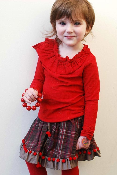 FALL 2012 KIDS FASHION PREVIEW: Pom-poms, polka dots and ruffles: buyers are responding to Sophie Catalou's freewheeling styles for Fall 2012. A look they love: The Asymmetrical Tunic Top in rich ruby red and the Check Skirt with pom-pom trim.  (Most styles fit 12 months to 12 years).