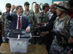 reuters:  Islamist Mohamed Morsy of the Muslim Brotherhood was declared Egypt's first democratic president on Sunday by the state election committee, which said he had defeated former general Ahmed Shafik with 51.7 percent of last weekend's run-off vote. He succeeds Hosni Mubarak, who was overthrown 16 months ago after a popular uprising. The military council which has ruled the biggest Arab nation since then has this month curbed the powers of the presidency, meaning the head of state will have to work closely with the army on a planned democratic constitution. READ MORE: Islamist Morsy wins Egyptian presidency with 52 percent  Morsey is ideologically different to many revolutionaries, but nevertheless a figure that they can call coalesce around against the SCAF junta.