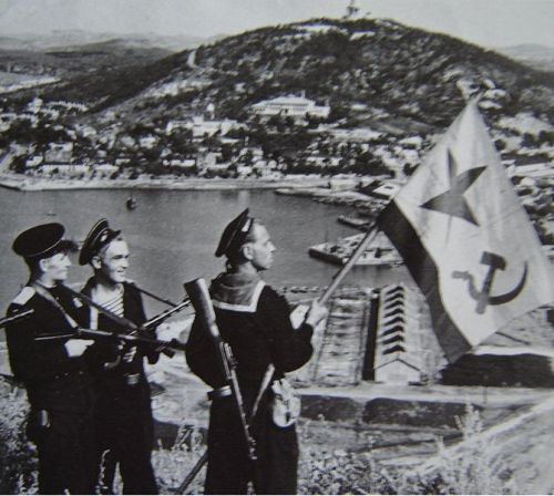 Soviet sailors raise the USSR's naval ensign over the city of Lushunkou in 1945 when they reoccupied the Liaodong and other parts of Inner ManchuriaLüshunkou is located at the extreme southern tip of the Liaodong Peninsula. It has an excellent natural harbour, the possession and control of which became a casus belli of the Russo-Japanese War (1904–1905). Japanese and then Soviet administration would continue until 1953. During the first decade of that period, it was world famous and was more significant than the other port on the peninsula, Dalian proper. In Western diplomatic, news, and historical writings, it was known as Port Arthur, and during the period when the Japanese controlled and administered the Liaodong (formerly Liaotung) Peninsula it was called Ryojun (旅順), the Japanese pronunciation of the Chinese characters in the city's name.