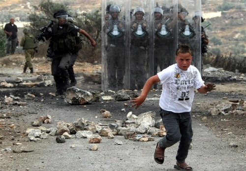A young Palestinian protester runs away from Israeli soldiers during a demonstration against the expropriation of Palestinian land by Israel in the village of Kafr Qaddum, near the West Bank city of Ramallah on June 22, 2012.