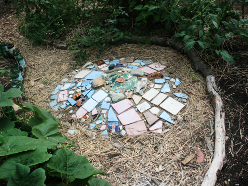 Yard art mosaic made from all recycled/reused materials and natural clay we dug from our own yard.  This sculpture is in the center of a lush keyhole vegetable garden.  For more of the artist's work, visit:  http://www.facebook.com/pages/Art-Adventures-with-Tikva-Adler/198903363467062