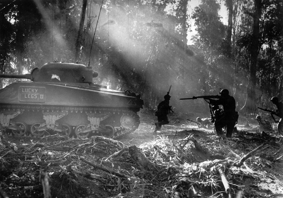 collective-history:  Following in the cover of a tank, American infantrymen secure an area on Bougainville, Solomon Islands, in March 1944, after Japanese forces infiltrated their lines during the night. (AP Photo)