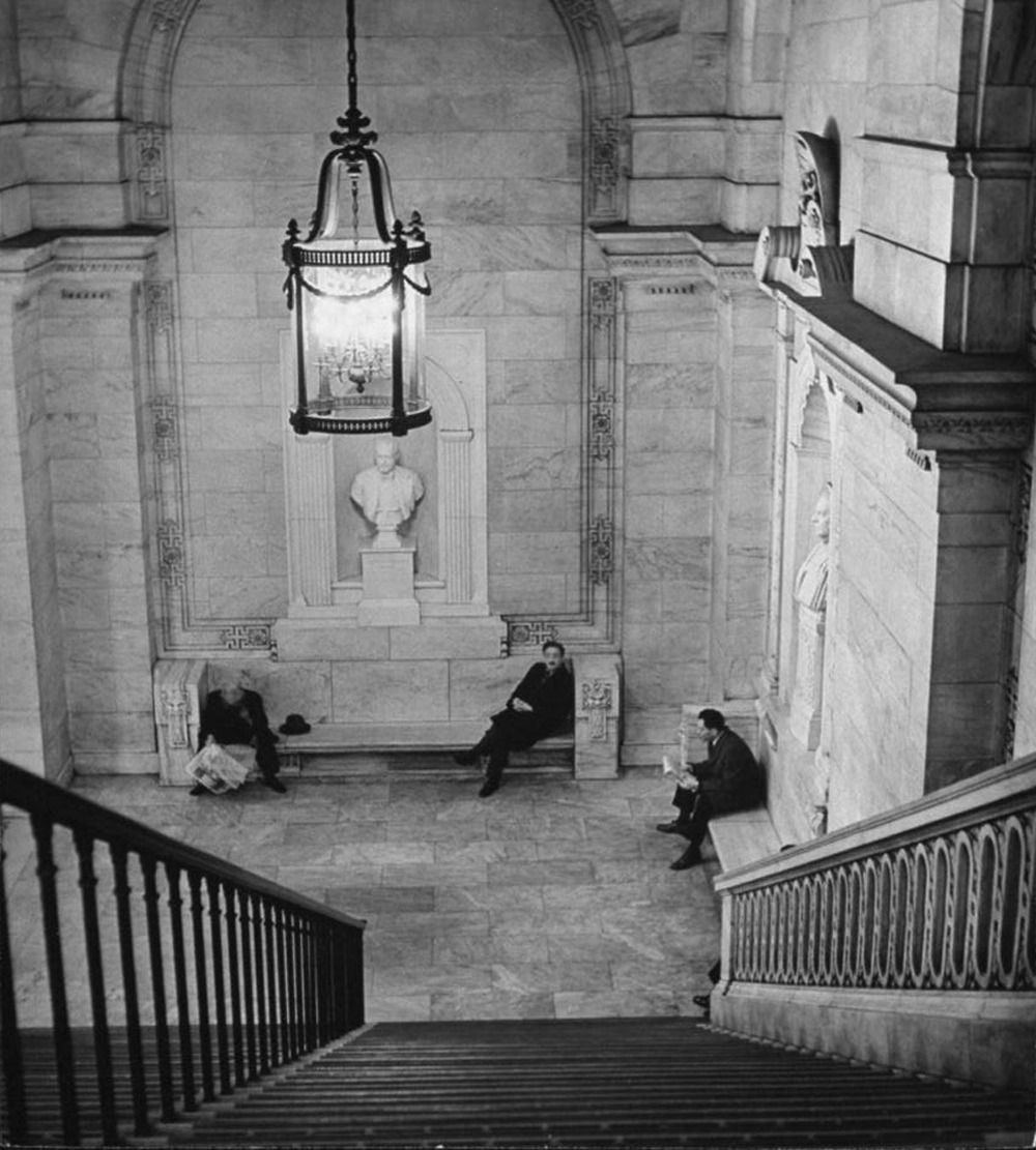 Men sitting on stone benches in New York Public Library, 1944. By Alfred Eisenstaedt