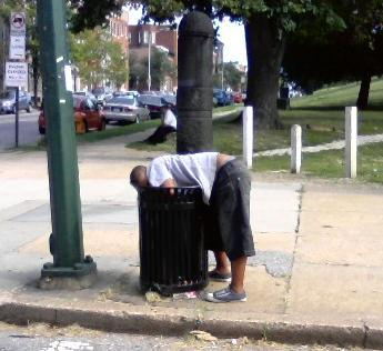 "Location: Corner of Eastern Ave and Patterson Park Ave, Baltimore, MDRating: 4.5Description: OK, who hasn't been in this situation. There you are walking down Eastern Ave minding your own business when you walk by a garbage where some idiot threw out half a perfectly good sandwich because they're rich or something and don't eat food that's ""spoiled"". Naturally, you reach into the can to save the sandwich and BAM! You pass out in the can because you've been shooting dope all morning and chewing Oxycodone like they're Chiclets. This is practically a daily occurrence as far as I'm concerned so I honestly don't know why anyone would find this picture strange, but I guess I'll rate it anyway for those of you who don't live in Baltimore."